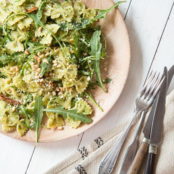Grünes Erbsen-Pesto schmiegt sich um Salat aus Farfalle, getrockneten Tomaten und Rucola. On top gibt's veganen Parmesan aus Cashews und Hefeflocken.