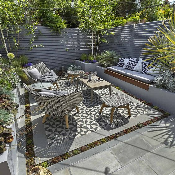 Kleine tuin met verhoogde plantenbakken en geintegreerde bank