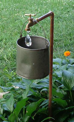 Vintage garden décor.  Use red water pump, and use the idea of the crystal hanging to give the illusion of water.  I like it.