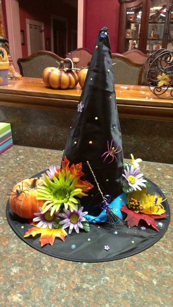 I made this with a plain small witch hat.  I added ribbon, puff paint, some bling, flowers, a pumpkin & made the witches broom with sticks from my yard!  Hat #1