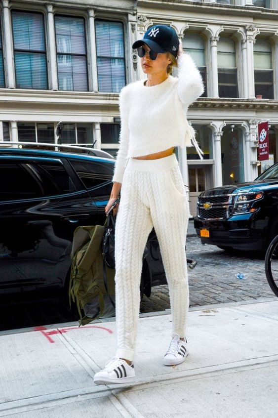 Gigi Hadid in a white sweater, joggers, and sneakers.: