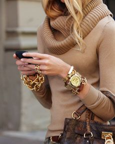 Nude sweater and lots of gold chunky jewelry.