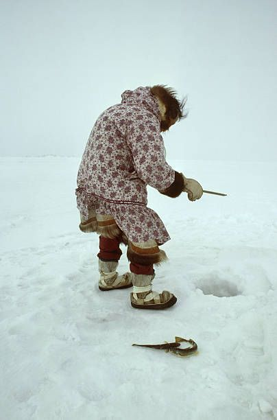 Mature Inuit woman wearing parka ice fishing.