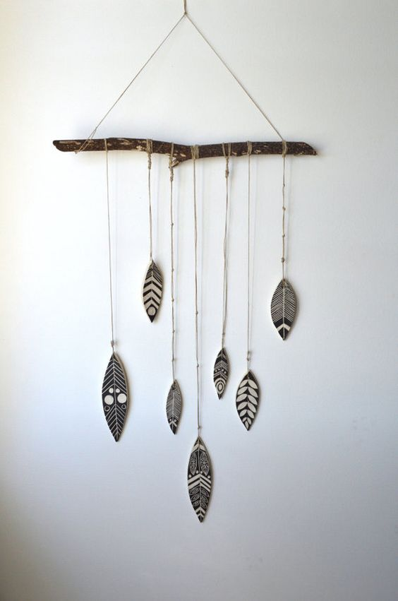 Hand carved ceramic feathers tied with hemp, hung from natural tree branch. Branch measures 15- 17 inches, ceramic feathers hang 24-26 inches. Can be hung