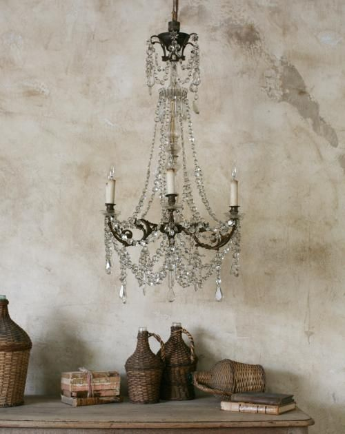 Mottled distressed and weathered walls in an Old World vignette with crystal chandelier, vintage vintner's baskets, and old books. Weathered Walls & Déshabillé Lovely. #oldworld #walls #mottled #distress #crystalchandelier #vintnerbasket #European #eloquence