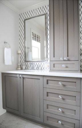 bathroom with lattice tile, gray vanity, crystal knobs, white counters, chrome fixtures, built in storage tower: