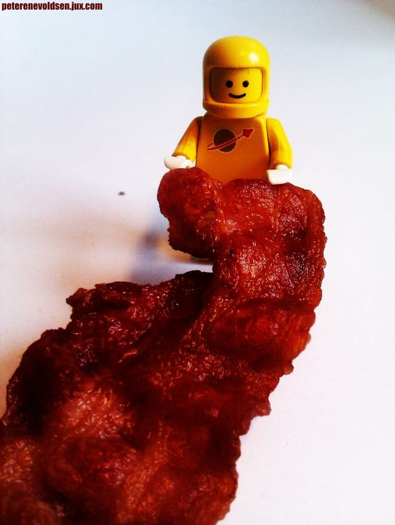 LEGO astronaut with a huge piece of bacon.