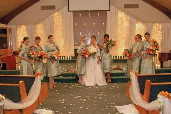 Bridal party...sage green dresses, accent or orange..lighted contemporary glass waterfall in background.