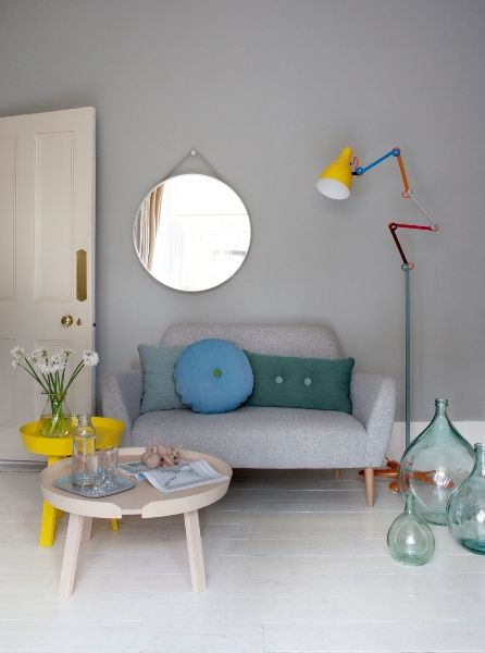 Buttoned sofa, strap mirror, multicoloured floor lamp, 'Around' coffee tables, and vintage bottles.