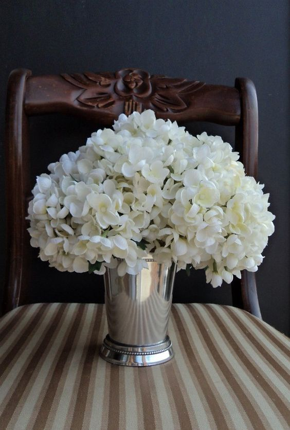 Mint julep filled with hydrangeas white flowers kissing