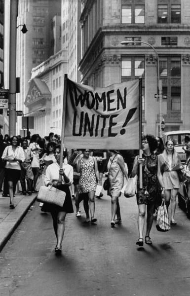 """Signs saying """"Women Unite"""" carried by women supporters during """"Women's Liberation"""" demonstration on Fifth Avenue and on Wall Street. New York, 1970."""