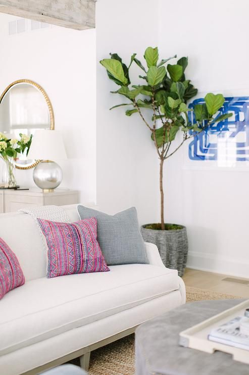 A White Sofa Sits On A Jute Rug And Is Complemented With Pink And