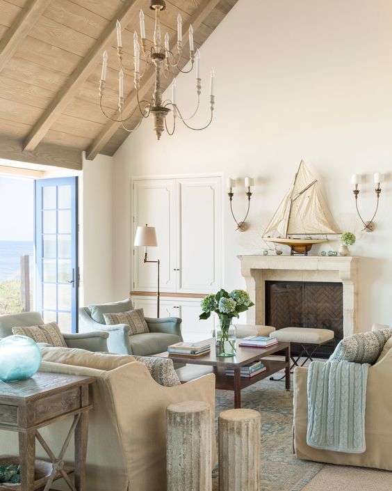 A stunning lofty and lovely living room in a Cali beach house by Giannetti Home, has Aidan Gray lighting, rustic vaulted ceiling, and linen upholstered furniture. #frenchcountry #beachhouse #giannetti