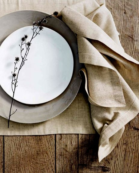 Open-grained plank table, linen napkin and placemat, hand-thrown stoneware, wildflower sprig. A feast for the senses and there hasn't been any food served yet!