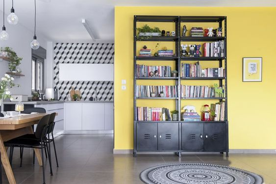 Scandinavian kitchen, yellow wall and black iron bookcase