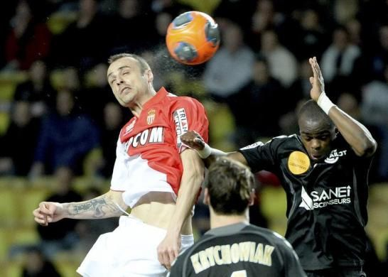 Monaco's Dimitar Berbatov (L) challenges Stade de Reims' Prince Oniangue for the ball during their French Ligue 1 soccer match at the Louis ...