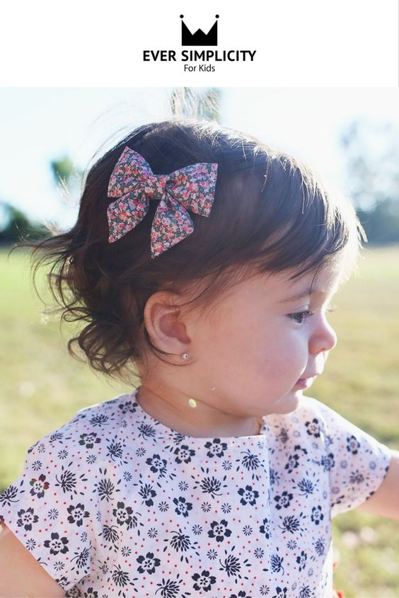 """Hand-crafted sailor bows for the little ladies! A beautiful sailor bow in a pink scatter pattern of Liberty of London. You can choose a nude nylon band (one size fits all) or a partially lined alligator clip. Bow fabric 100% cotton.  Bow measures approximately 3"""" x 2.5"""" Each bow is hand-cut, pressed, and sewn with love by our team in California.  We guarantee our bows 100%! By Ever Simplicity."""
