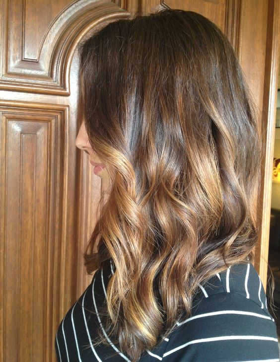 Slightly A lined medium length haircut with face framing warm blonde balayage highlights, dressed up