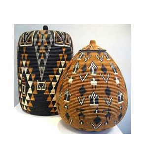 Baskets by Angeline Masuku. (South Africa) wearing in traditional coiled and over-stitched Zulu basketry' constructed of plat fiber, dyed with roots and berries.