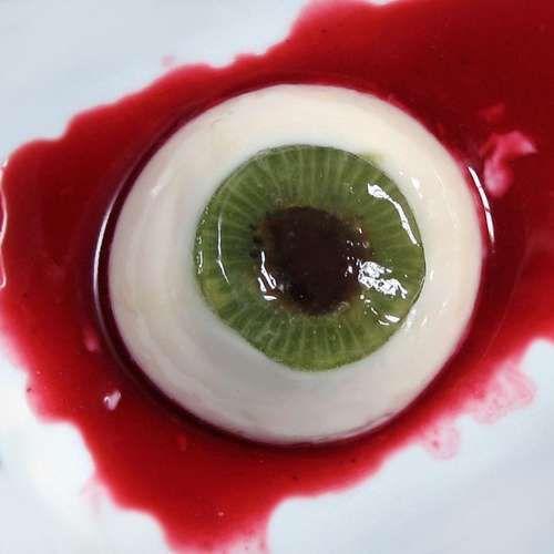 Gourmet Halloween dessert: coconut panna cotta with kiwi and raisin iris with raspberry coulis 'blood'.