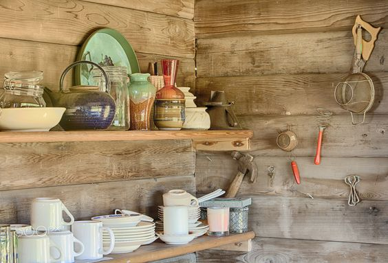 Kitchen Shelves - A still life image of kitchecn shelves in an old log cabin showing the plates, cups, bowls and other houswares arranged on each shelf.