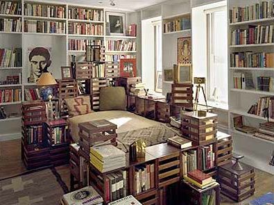 Designer's bed surrounded by cube crates for his books
