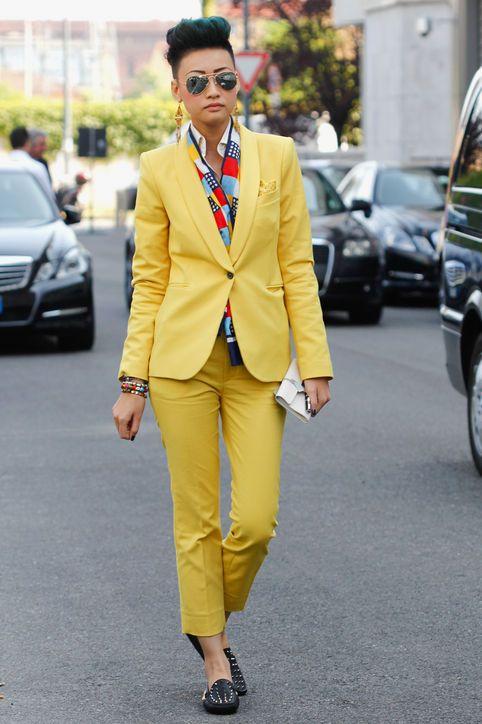 Esther Quek. bright orange suit with bold patterned shirt, black flats.