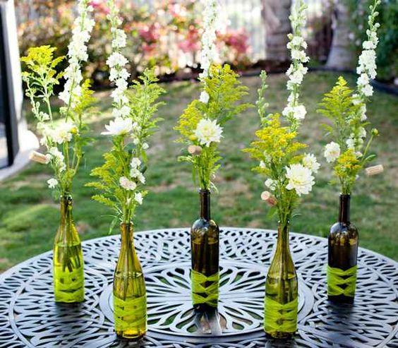centros de mesa con flores y botellas recicladas