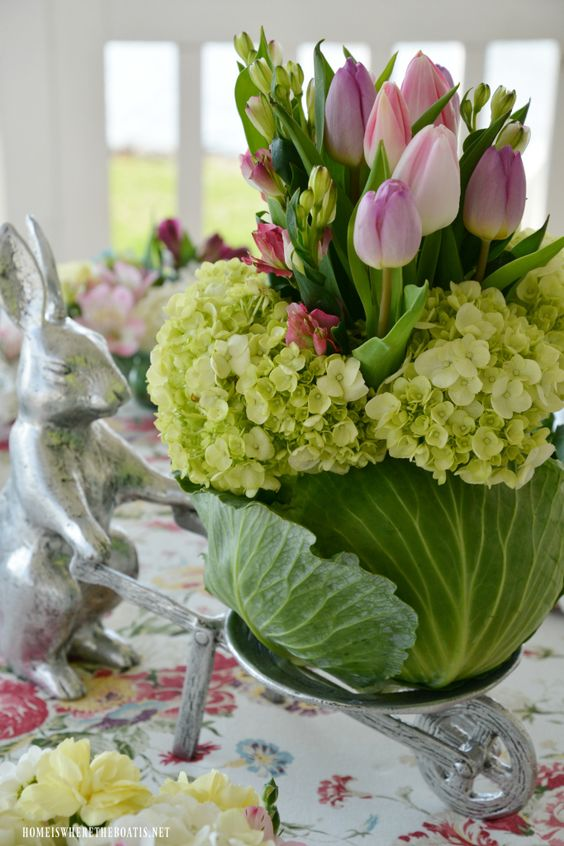 Bunny wheelbarrow with blooming cabbage flower arrangement | ©homeiswheretheboatis.net #spring #tablescape #bunnies