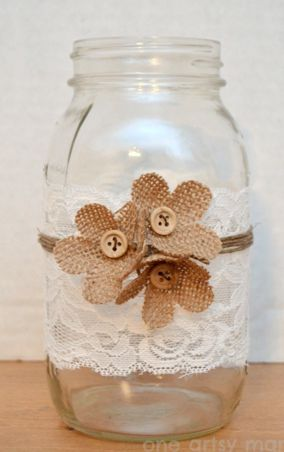 Tarro de vidreo reciclado y decorado con puntilla, cuerda, flores de tela de saco y botones. Una manualidad con mucho gusto.