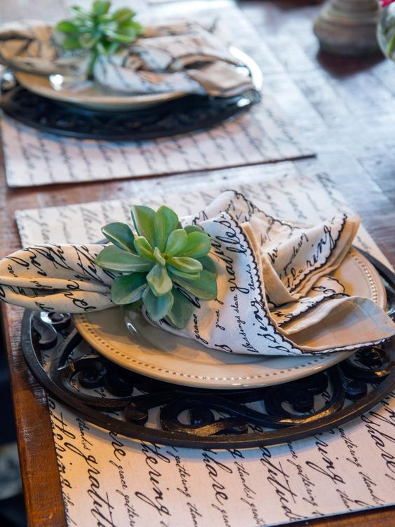 In the dining room, the rustic wood dining table is staged with distinctive wrought-iron charger plates, ceramic dishware and table linens covered in cursive script print.
