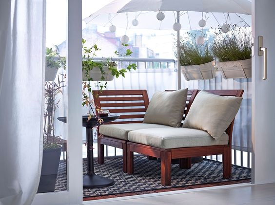 A balcony with brown wooden modular seating with beige seat/back cushions and a black round tray table