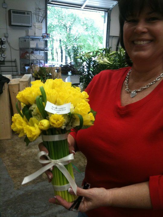Delightful daffodils. Julie models a sophisticated bridal bouquet of sunny yellow daffodils finished with a sophisticated banding of slender ivory ribbon.
