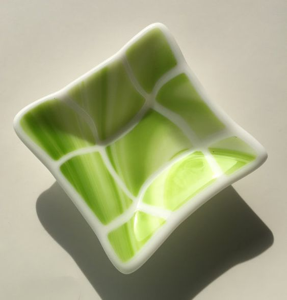 This handmade glass fused art dish is made with white glass and swirly lime green squares of glass. The dish measures 4 x 4 which has been slumped into a glass mold. It can be used as a simple art piece or a place for your jewelry, food uses, candle holder, your desk or just your trinkets. The dish is properly annealed in my kiln for strength and durability. It is food safe and I recommend hand washing. Please do not place in microwave or dishwasher. All pieces are packaged carefully for…