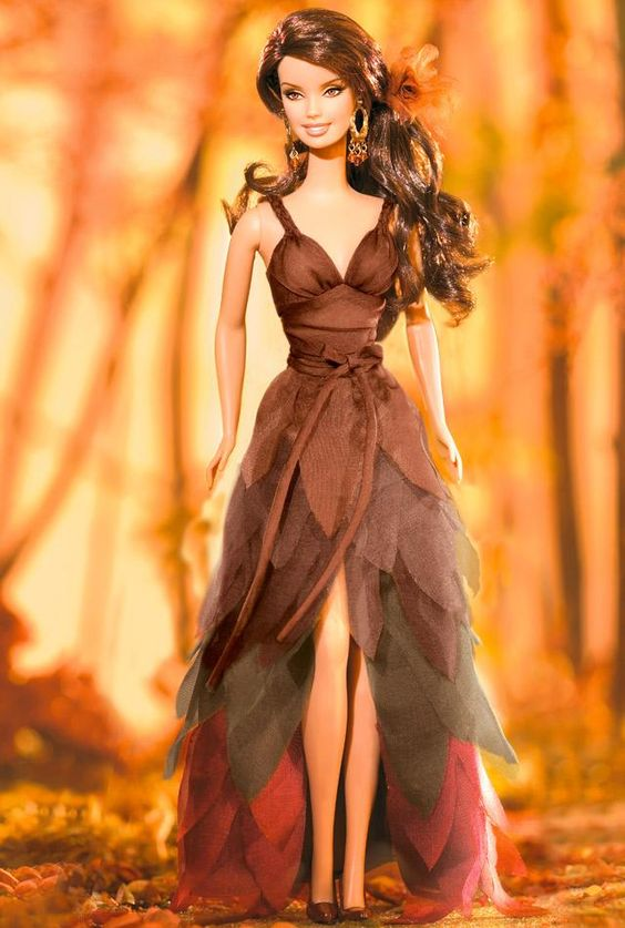 ~ I Dream of Autumn™ Barbie® ~   Fall is the inspiration for this dark haired beauty wearing a charmeuse gown with petal layers in shades of autumn. Golden earrings and a soft, rust-colored, iridescent chiffon hair ornament complete the ensemble.