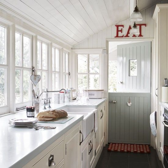 Wood-paneled country kitchen from house to home.  Love the sign and Dutch door and all those windows.