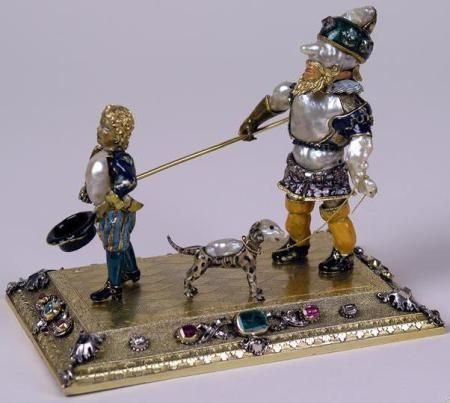 Germania / Staatliche Kunstsammlungen Dresden (SKD) Obiect decorativ creat de către aurarul Johann Heinrich Kohler (?-1736) înfăţişând un orb condus de un copil şi un câine; aur, argint, argint aurit, perle baroce, diamante, smaralde, rubine şi email. Dimensiuni: 12,7 x 10,4 x 8,2 cm.: