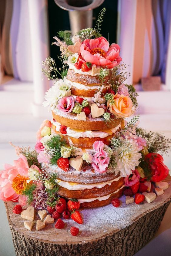 Naked wedding cake decorated with shortbread and flowers wow, kinda love this!