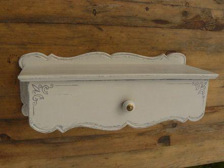 Jolie tablette murale en bois (chêne) relookée en blanc cassé patiné avec un tiroir décoré de fins motifs et d'un petit bouton de faïence blanche. L'intérieur est peint en  - 13706407