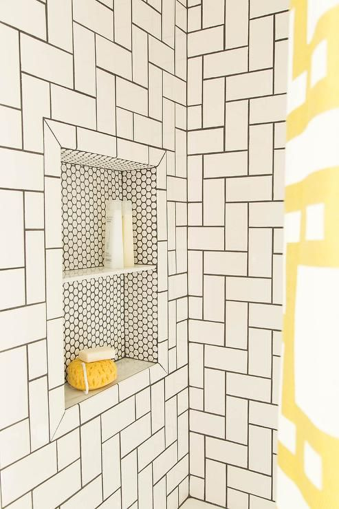 Simple white subway tiles take on a whole new look when laid out in a  geometric pattern with dark grout. A penny-tiled shower niche with shelf  add