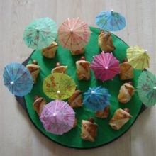 Een poppetje onder een parasol, gemaakt van bladerdeeg met een coctailworstje erin.