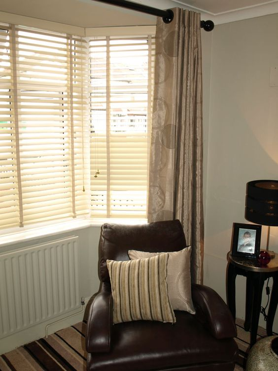 Chic eyelet curtains on a pole with wooden blinds fitted around ...