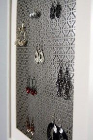 It's a framed grate you can find at Home Depot to hang your earrings!