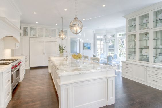 A pair of Restoration Hardware Victoria Hotel Pendants illuminate an extra-long kitchen island topped with white marble framing square sink and polished nickel faucet lined with white and blue counter stools.
