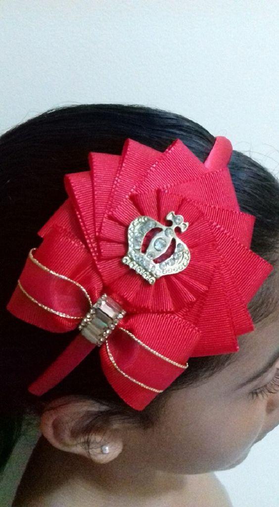 Tiara forrada, Flor e laço feito com fita gorgurão na cor vermelha. Aplicação de coroa e strass. 1 em estoque.