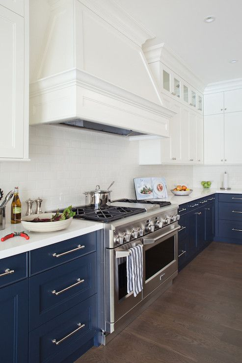 white and navy kitchen with white upper cabinets and navy lower cabinets accented with nickel hardware along with sleek white counters and a traditional subway tiled backsplash framing stainless steel Viking Range under tapered white wood range hood.: