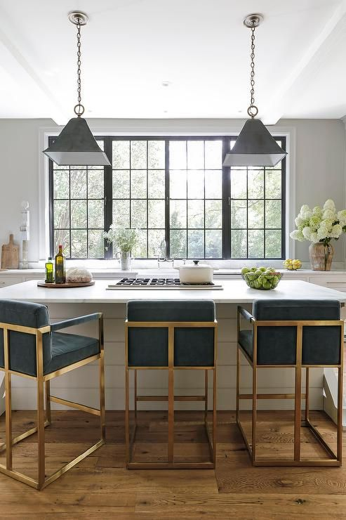 Blue velvet counter stools sit at a white shiplap island topped with a honed white marble countertop holding a gas integrated cooktop beneath black metal vintage lights.