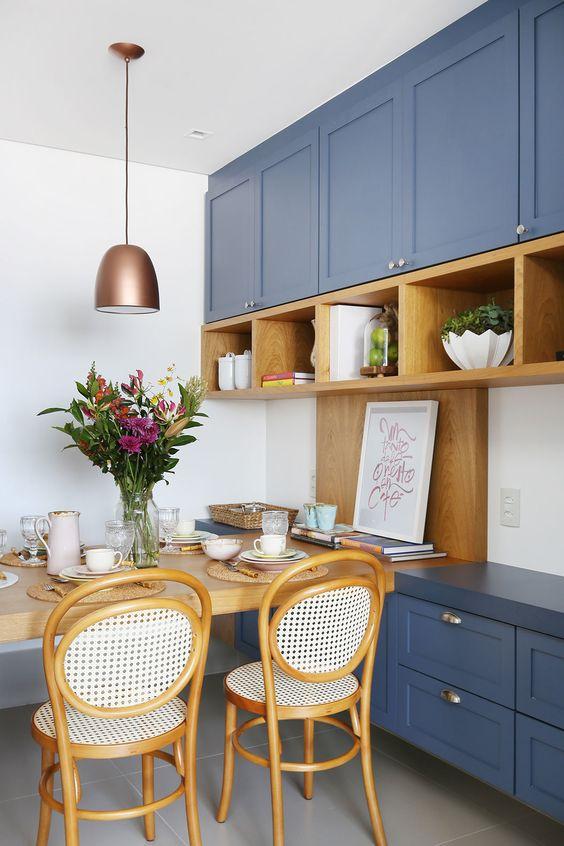 Decoração de cozinha e sala de jantar. Armário azul, nicho de madeira, quadrinho, mesa de jantar de madeira, cadeira de madeira, vaso com flores, pendente bronze. #casadevalentina #decoracao #decor