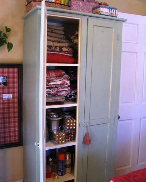 LRobb created a cozy sewing and crafts room from re-purposed flea market finds and leftover fabrics and paint. This vintage armoire holds fabrics, ornaments, and sewing and craft supplies.