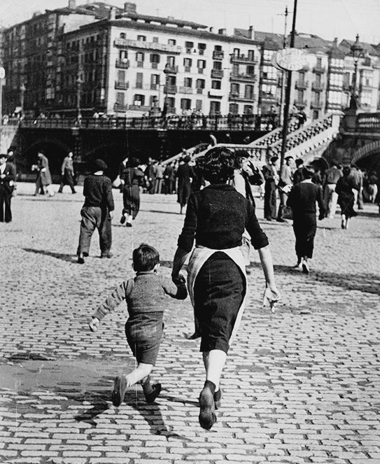 Robert Capa, Woman and child run after an alarm has sounded, Bilbao, 1937.